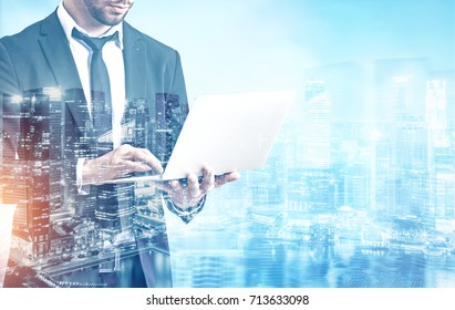 Close up of an unrecognizable young businessman working at his laptop standing against a morning city panorama. Mock up toned image double exposure