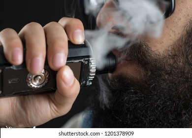 Close up of an unrecognizable young man smoking from a vape pen or vaporizer