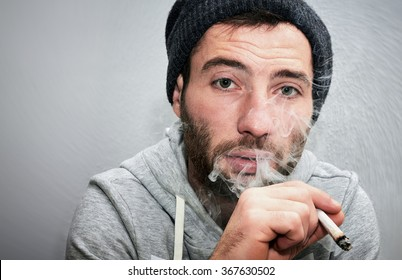 Close up of a unshaven man smoking a joint.