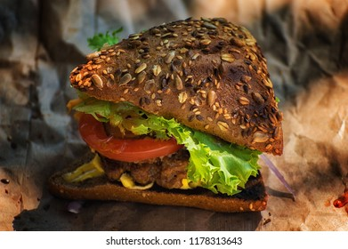Close uo of a hamburger with vegetables on the background of parchment