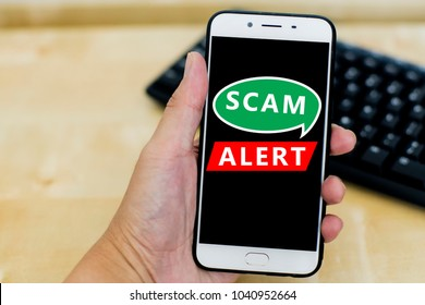 Close uo image of hand holding a smartphone with black screen and text scam alert. Internet issue and viral. Shallow DOF, selective focus.
