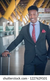 Close uo of one young and attractive black businessman is waiting for a car outside of the airport wearing a black suit with a red tie and carrying a suitcase.