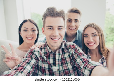 Close uo photo of four youngster in checkered shirt that make selfie on the front camera of their smartphone show v-sign and do big toothy smile