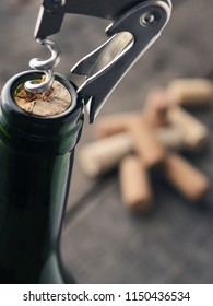 Close uo of a wine bottle with bottle opener on a dark background