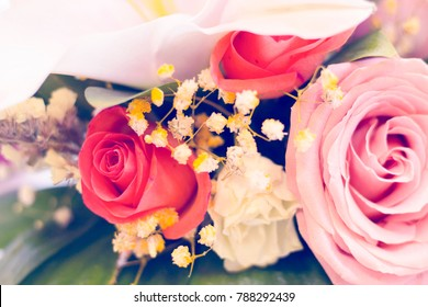 A close up uof a bride's bouquet with red and pink roses. St. Valentines, anniversary, wedding concept with copy space. Space for your text or product display.