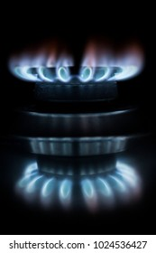 Close uop of the flames of a hob and its reflections