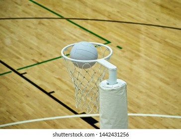 A close up, above eye level view of a Netball Ball entering a Netball Goal. The ball sits in the centre at rim level above the mesh nylon net. Wooden floorboards of an indoor court as the background.