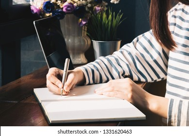 Close up. Asian Female writing on a notebook with computer laptop in the coffee shop.