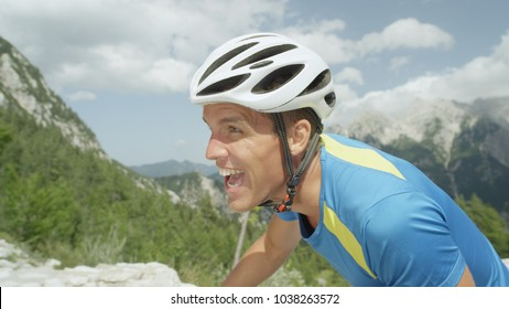 CLOSE UP: Athletic man going through grueling exhaustion during intense cycling tour in the steep mountains. Fit pro cyclist fighting an uphill battle as he climbs a steep mountain with his bicycle.