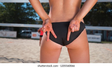 CLOSE UP: Athletic young woman in a black bikini showing hand signals to her teammate while playing beach volleyball on a sunny day. Unrecognizable female beach volleyball player showing hand gestures