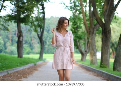 Close up, attractive young blonde woman in dress walking in summer park