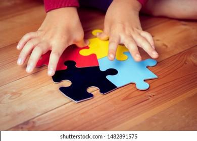 Gros plan: Les mains d'un enfant autiste jouant un puzzle symbole de la sensibilisation du public aux troubles du spectre autistique. Journée mondiale de sensibilisation à l'autisme 2 avril, Soutien, Compréhension et acceptation. Santé des enfants.