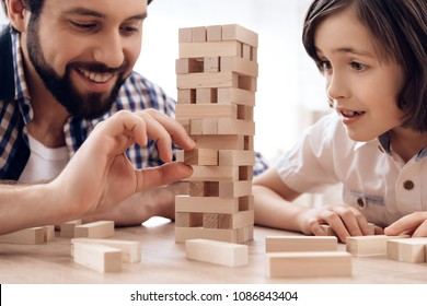 Close up. Bearded father with small son plays at home. Man removes wooden blocks from tower. Board game.