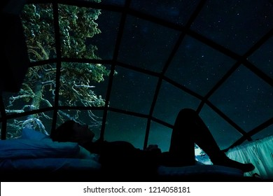 CLOSE UP: Beautiful female tourist lying in bed and watching the night sky. Happy traveler girl having fun observing the night sky and waiting for spectacular aurora borealis from the glassy igloo.