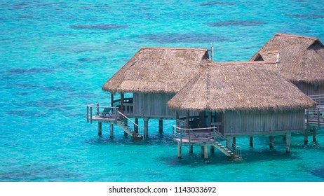 CLOSE UP: Beautiful wooden bungalows surrounded by breathtaking emerald ocean water in the stunning Maldives. Breathtaking tropical sea and oceanfront luxury hotel apartments near paradise island.