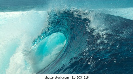 CLOSE UP: Big foaming barrel wave, glimmering in the bright summer sunshine, rages past the camera and towards tropical island. Breathtaking empty wild tube wave breaking near picturesque Tahiti.