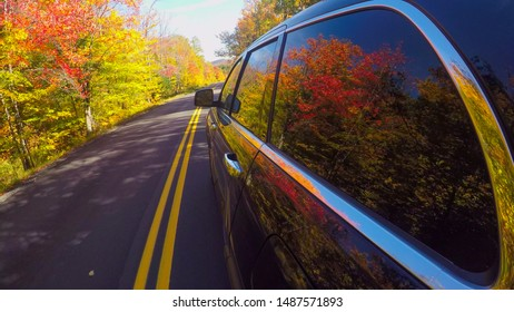 CLOSE UP: Black SUV car driving along the gorgeous forest road past the colorful trees on sunny autumn day. People on leaf peeping road trip traveling through bright autumn forest in sunny fall