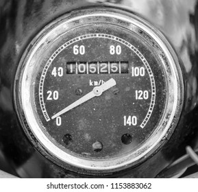 A close up, black and white photo of a weathered, vintage motorcycle speedometer and odometer with classic white numbers and a white needle.
