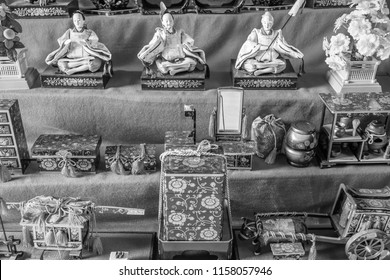 A close up, black and white photo of antique porcelain dolls in silk kimonos on display with ornate doll furniture during the Dolls Festival ('Hinamatsuri') in Japan.