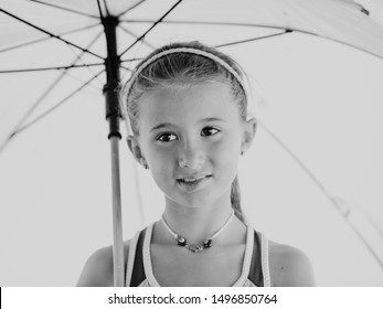 Close up, black and white shot of a beautiful girl with a half smile, headband and ponytail folding an umbrella looking away