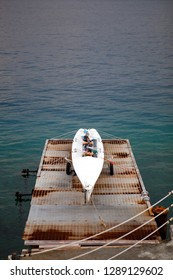 Close up. The central port (harbour) of Messina with a white kayak (canoe) on the pier. Сloudy day. Messina. Sicily. Italy