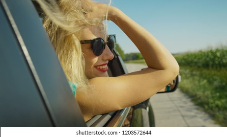 CLOSE UP: Cheerful blonde haired girl adjusts her long hair while driving through picturesque sunny countryside. Young female tourist's beautiful long hair gets messy as she drives along rural road.