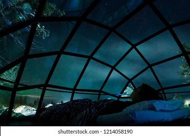 CLOSE UP: Cheerful female tourist having fun observing the night sky from the cool glassy house. Young traveler girl lying in bed and waiting for the famous northern lights to appear in the dark sky.