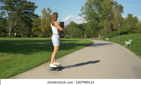 CLOSE UP: Cheerful millennial woman holds her puppy while riding an electric longboard through the scenic green park. Unrecognizable girl and her miniature pinscher longboard through park on sunny day