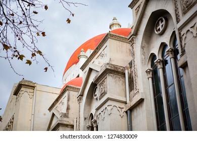 "Close up, ""Chiesa Cattolica Parrocchiale S. Giuliano"" - Italian Catholic perish church of Saint Giuliano with red domes and gray stone walls. Cloudy sky. Messina, Sicily, Italy."