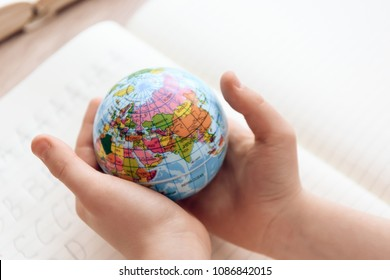 Close up. Child holds small globe in hands. Studies of geography. Self education concept.