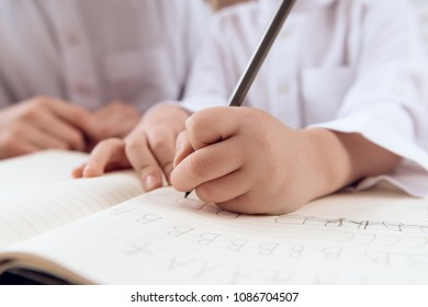 Close up. Child learns spelling. Boy writes letters in copybook.