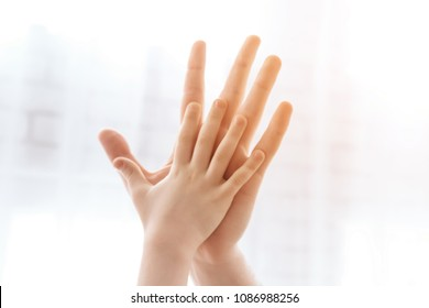 Close up. Child palm gives five to palm of adult male. Happy relationship between parent and kid.