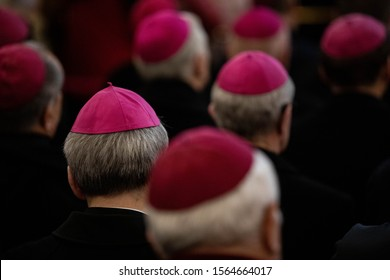 close -up of clerics in the amaranth zucchetto (form-fitting ecclesiastical skullcap) praying during the mass in the chapel