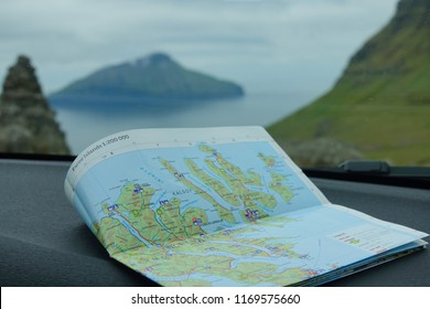CLOSE UP: Colorful map of Faroe Islands rests on the dashboard of a modern car driving down scenic road in the picturesque countryside. Unfolded map of Kalsoy sits on near the windshield of a car.