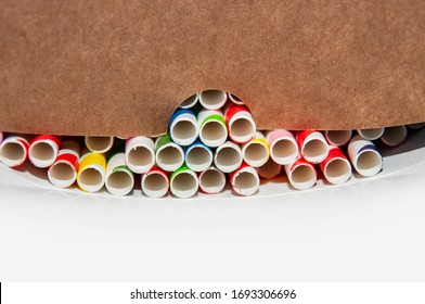 Close up, colorful paper straws in a cardboard box, gray background