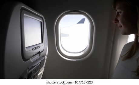 CLOSE UP: Content businesswoman on transatlantic flight looks through her window. Young woman looks through the aeroplane window during a long flight before pulling down the blind before landing.
