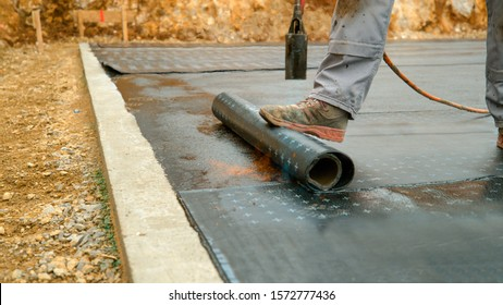 CLOSE UP: Contractor burns a black roll of tar paper over concrete foundation. Man melts a roll of tar onto the foundation of a house under construction. Unrecognizable man laying down a roll of tar.