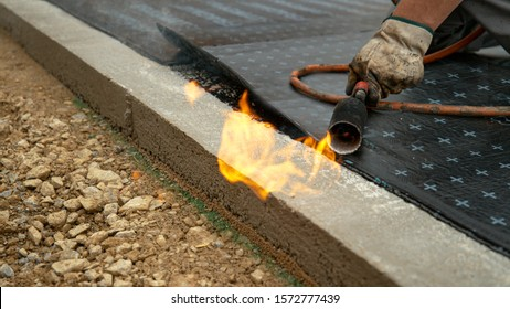 CLOSE UP: Contractor wielding a propane torch burns a roll of tar paper over the concrete foundation of a building under construction. Laborer waterproofing a building by melting a bitumen on ground.