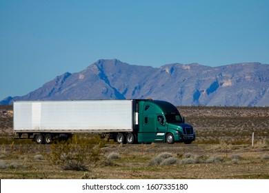 CLOSE UP: Cool shot of barren landscape surrounding a green semi-trailer truck transporting cargo across the Utah Desert. Dark green 18 wheeler crosses the arid landscape deep in the Utah desert.