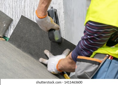 Close up, cropped photo hands with stapler of qualified and mature contractor in protective uniform wear. Man attach special waterproof bitumen membrane on roof top of new modern building construction