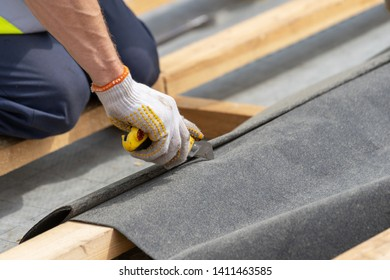 Close up, cropped photo of professional and qualified installer standing working on rooftop of new modern building construction. Man using knife and cutting special waterproof bitumen membrane
