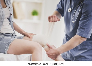 Close up. Doctor in Blue Uniform Comfforting Leg of Sitting Young Woman in Doctor Office. Traumatology Medical Devices. Medical Treatment in Clinic and Healthcare Professional Concept.