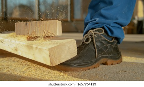 CLOSE UP, DOF: Detailed shot of a painful work accident as a heavy plank falls on an unrecognizable worker's foot. Worker sawing wood drops a beam on his foot. Unlucky construction site accident