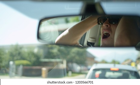 CLOSE UP, DOF: Reflection of a frustrated young man yelling at the car in front of him as he drives through the morning rush hour traffic. Handsome Caucasian male experiencing a fit of road rage.