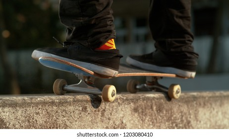 CLOSE UP, DOF: Unrecognizable man wearing funny colorful cannabis socks and skateboarding in the outdoor park grinds a concrete ledge. Cinematic shot of young athlete doing a cool skateboarding trick.