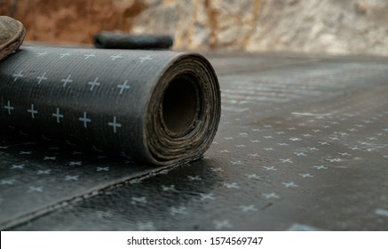 CLOSE UP, DOF: Unrecognizable worker rolls out black tar paper with his foot while waterproofing a house. Heat slowly melts a thick roll of black bitumen onto the concrete foundation of a building.