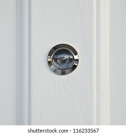 close up, door lens peephole on white wooden texture
