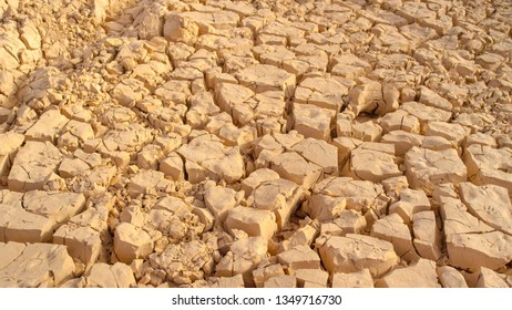 CLOSE UP: Dried up light brown soil cracking in the scorching hot summer weather. Aftermath of devastating natural disaster leaving the ecosystem dry and lifeless. Beige soil cracking during drought.