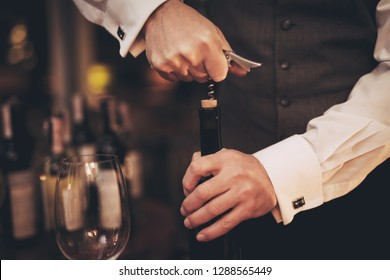Close up. Elegant sommelier uncorking bottle of wine in restaurant. Wine tasting. Sommelier tasting wine in restaurant.