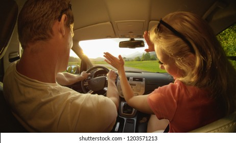 CLOSE UP: Energetic Caucasian couple having fun during their summer road trip through the sunny countryside on a perfect summer morning. Cheerful young boyfriend and girlfriend dancing in their car.